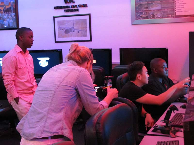 TAM participants learning to fly using flight simulator programs.