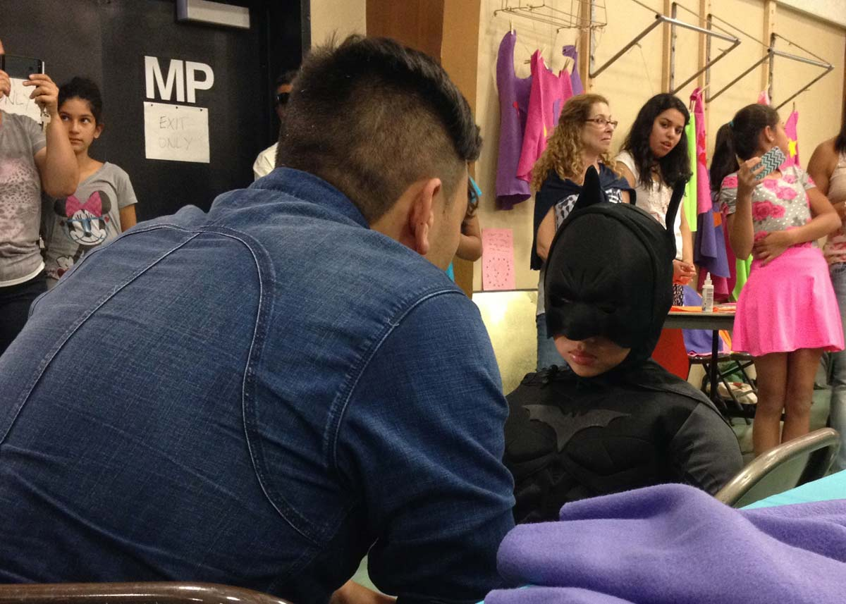 Toan and Nico Castro, dressed in a Batman outfit