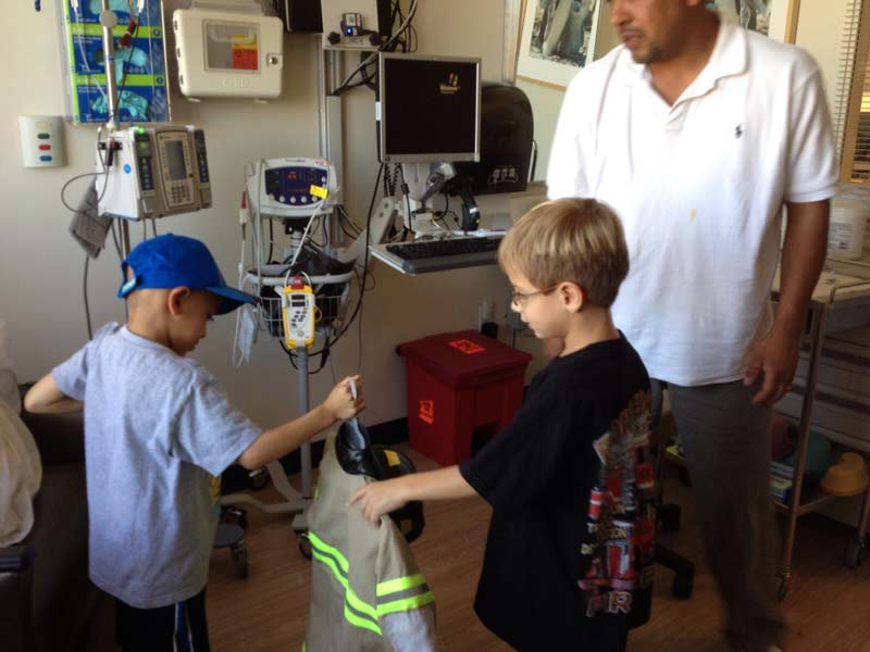 Nico Castro giving out Halloween costumes to other kids at the hospital